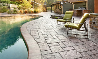 stamped concrete pool deck with sunset in the background